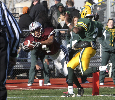 Josh Batista (4) of Lynn English scored first period touchdown during the Thanksgiving Day football game between Lynn Classical and Lynn English at Manning Field in Lynn. Classical's Jordan Brown (2) was on right.