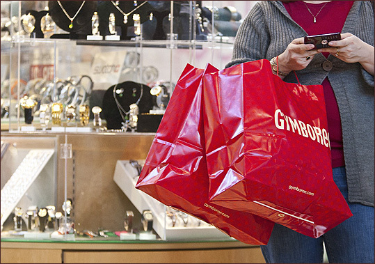A woman uses a cell phone as she holds shopping bags at South Park mall in Charlotte, N.C.