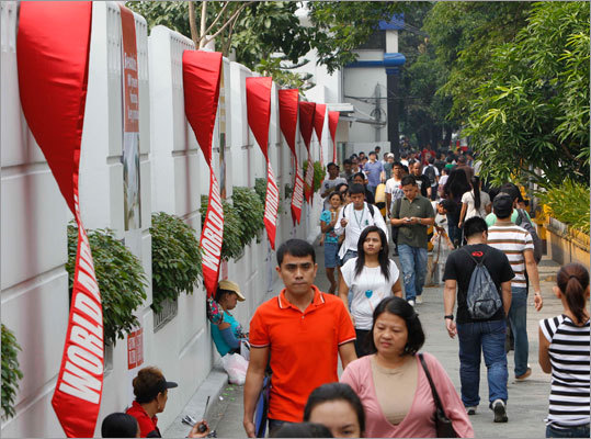 People walked past huge red ribbons symbolizing AIDS awareness that were hung from the walls of the Regional Headquarters of the World Health Organization in Manila.