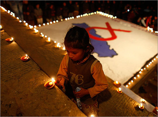A Nepalese child lit candles in front of a painting that depicts the Nepal map with a red ribbon, at an event to mark World AIDS Day in Kathmandu.
