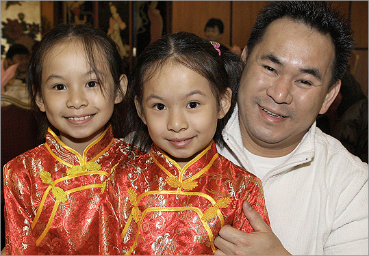 Dec. 10 in Boston From left: Twins Natalie and Valerie Ngo with their father, Jack Ngo, all of Quincy.