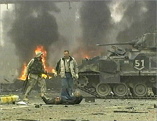 A television image showed a US soldier at the blast scene as an injured man lay in the road after a suicide bomber detonated 1,000 pounds of explosives in a pickup truck outside the headquarters of the US-led coalition in Baghdad on Jan. 18, 2004. Some 20 people were killed in the attack.