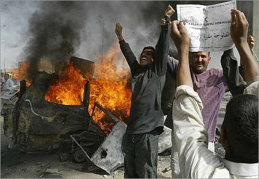An Iraqi boy held a leaflet in broken English that read 'Fallujah, the cemetery of the Americans,' as people celebrated near a burning car in Fallujah, 31 miles west of Baghdad, on March, 31 2004. Insurgents killed four contractors with the Blackwater security firm, then mutilated the bodies, dragged the charred remains through the streets, and hung two of the corpses from a bridge. The event triggered a massive US military siege known as the Battle of Fallujah.