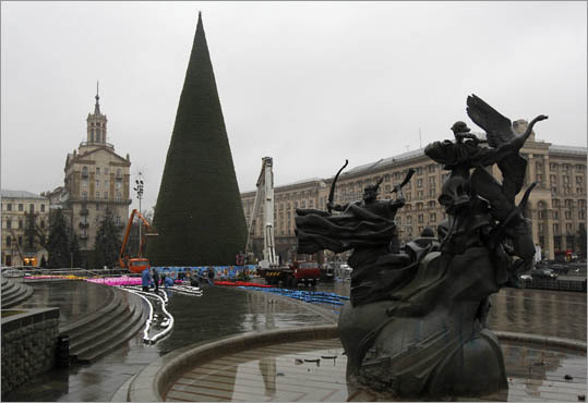 8. Ukraine Minimum vacation: 18 days Public holidays: 9 (Ukraine) Pictured: Municipal workers decorate a New Year's tree in the rain in central Kiev.