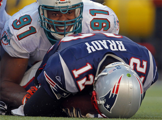 Miami Dolphins linebacker Cameron Wake (top) reacted after sacking New England Patriots quarterback Tom Brady during the second quarter.