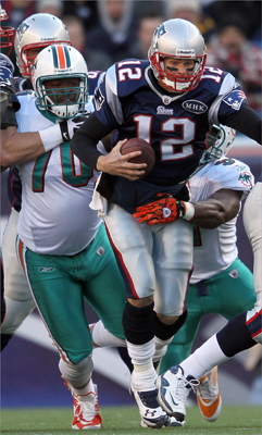 Tom Brady was brought down by Kendall Langford (70) and Cameron Wake (91) of the Miami Dolphins in the second quarter.