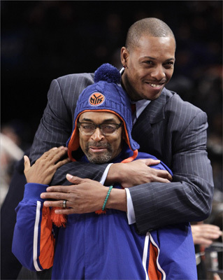 Boston Celtics forward Paul Pierce, rear, embraces director and New York Knicks fan Spike Lee before the Knicks' 106-104 victory over the Celtics in the season-opening NBA basketball game, at Madison Square Garden in New York, Sunday, Dec. 25, 2011. Pierce sat out the game with a bruised right heel. (AP Photo/Kathy Willens)
