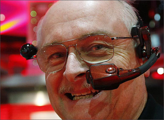 Jeffrey Jacobsen wore a Golden-i handsfree computing and communication headset in the Verizon booth. The device, set to be marketed by Motorola and Verizon later this year, allows the user to control and see his computer remotely. It will have video, bluetooth, Wi-Fi, GPS, and cellular capability. The device is expected to have broad applications in the law enforcement, medical, and manufacturing fields before going into the consumer market.