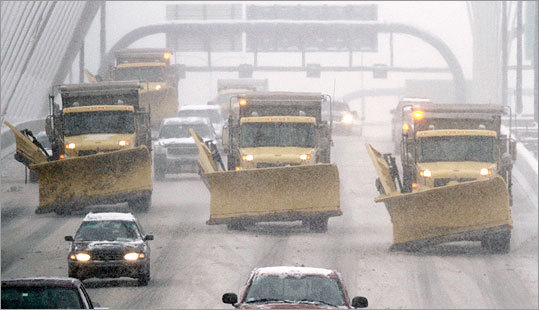Snow plows drove on I-93 over the Zakim Bridge into Boston.