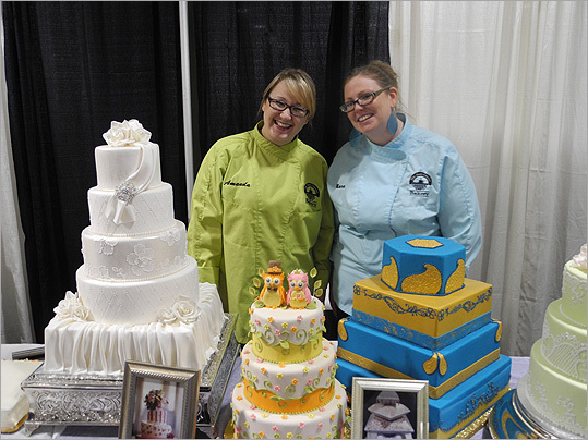 Amanda Russell (left) and Mara Mahoney of Bean Counter Bakery, located in Shrewsbury and Worcester, showed off their sample wedding cakes.