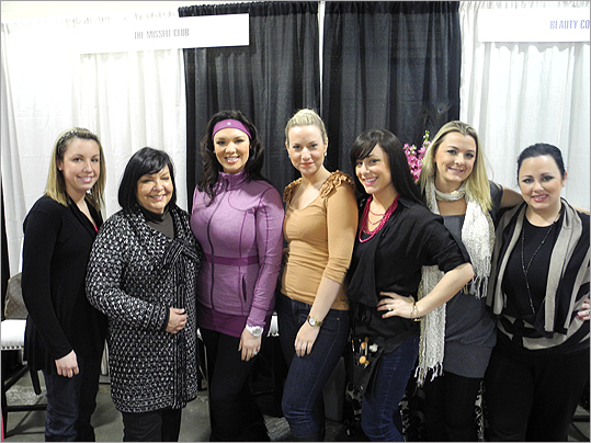 Katie Boyd (in purple) of the Style Network show 'Wicked Fit,' posed with her mother and sister (left) who were at the show representing her pageant gym, The Miss Fit Club, of Wellesley, and employees of Beauty Couture (right), in Lexington.