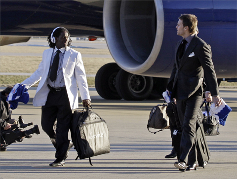 New England Patriots wide receiver Deion Branch, left, talked to Tom Brady as they arrived at the Indianapolis International Airport for Super Bowl XLVI.