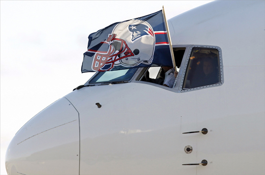 The New England Patriots' team flag was held out of the cockpit window as the charter flight arrived in Indianapolis.