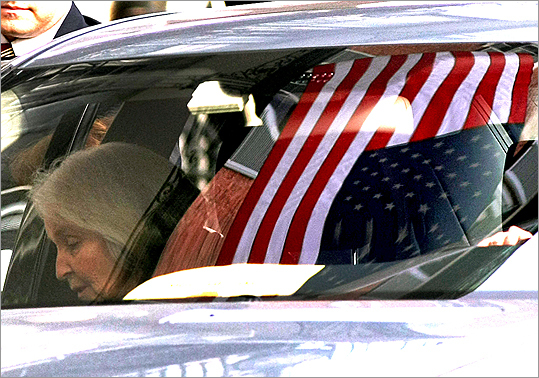 A flag hanging on the Parkman House was reflected in a windshield as White's wife, Kathryn, arrived for the wake.