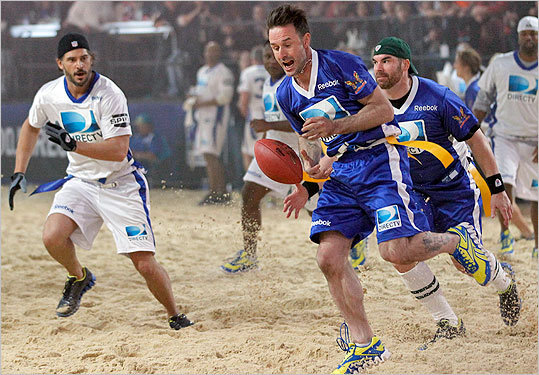 David Arquette (center) dropped a pass while fellow actors, Brandon Molale (right) and Joe Manganiello (left) ran behind him during the Celebrity Beach Bowl.