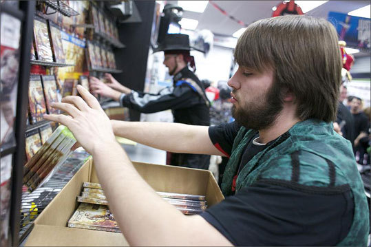 Tom Sharkey placed new copies of the Curt Schilling game 'Kingdoms of Amalur: Reckoning' on shelves at Game Stop.