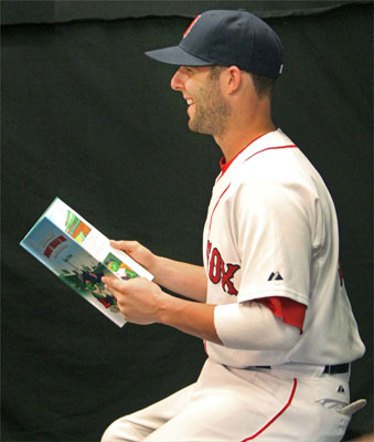 Some players, including Dustin Pedroia, were asked to pose with a children's book called 'Wally the Green Monster's Journey Through Time - Fenway Park's Incredible First Century.' Pedroia was the author of this edition of the book, which is part of a series.