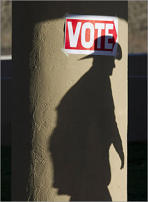 A shadow of a man wearing a cowboy hat fell on a pillar as he entered the polling place at Wickenburg Community Center in Wickenburg, Ariz.