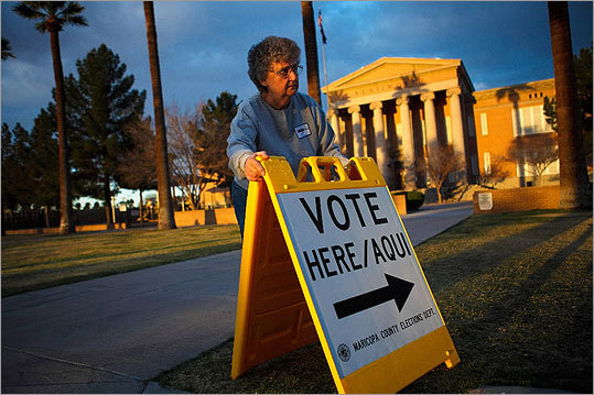 Election day volunteer Vicki Groff placed a sign to direct voters to a polling station at Kenilworth School in Phoenix on Tuesday morning as the sun rose.