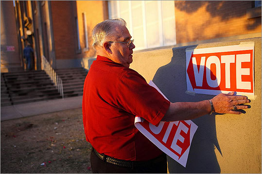 An election day volunteer placed signs to direct voters to a polling station in Phoenix.