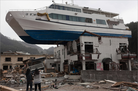 April 16, 2011 A catamaran sightseeing boat that was thrown by the tsunami onto a two story building in the town of Otsuchi, Iwate prefecture, was there a month after the tsunami when this photo was taken. But now, one year later, the boat has been moved and much of the rubble that littered this fishing port has been cleared. But the town remains paralyzed, unable to rebuild, and unwilling to abandon.
