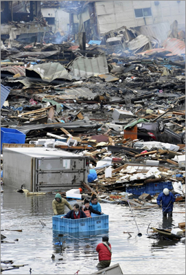 March 12, 2011 People used a floating container to escape from floodwater after the tsunami and earthquake struck in Kesennuma City, Miyagi Prefecture, in northeastern Japan. Japan confronted devastation along its northeastern coast, with fires raging and parts of some cities under water.