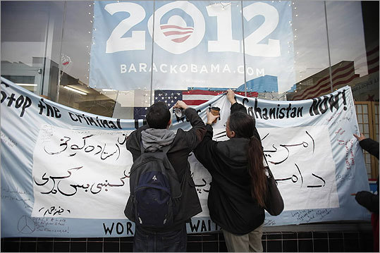 Two anti-war demonstrators attached a banner outside President Obama's campaign headquarters in Oakland, Calif., during a vigil for the victims on March 12.