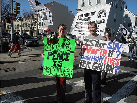 Signs held by people who walked with Veterans For Peace.