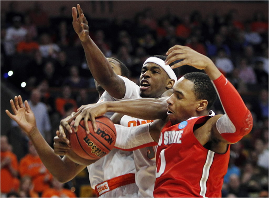 Syracuse forward C.J. Fair, left, and Ohio State forward Jared Sullinger (0) fought for a rebound during the first half of the East Regional final game in the NCAA men's college basketball tournament at the TD Garden in Boston on Saturday.