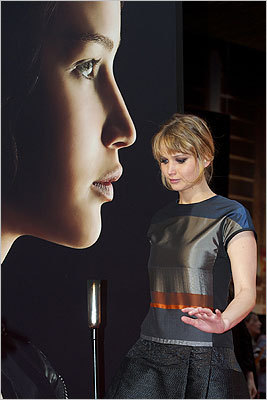 Jennifer Lawrence in front of a 'Hunger Games' poster.