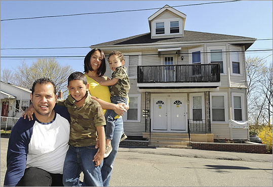 Isaac and Norma Morales posed with their children, Jacob, 5, and Isaac, 3, April 7 outside their Lynn, Mass. home, which they were able to keep with the help of a loan modification with Wells Fargo & Co.