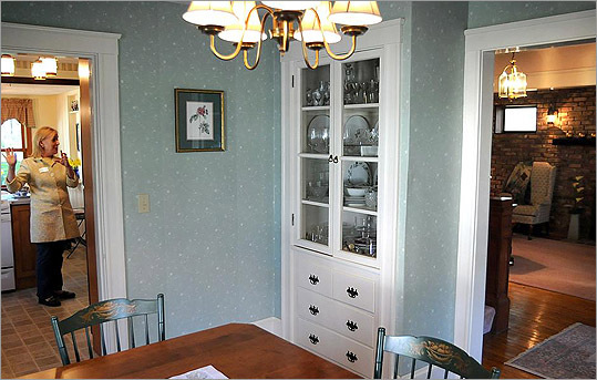A small dining room off of the front foyer has a built-in china cabinet and fireplace.