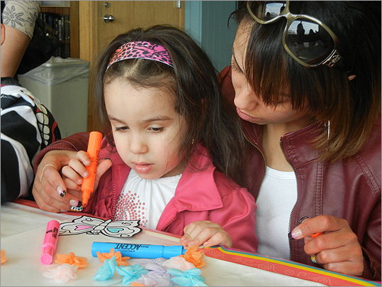 Skye, 3, and Erica Corona from Dorchester colored a butterfly at the arts and crafts table.