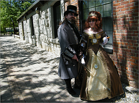 "Jessica Jackson, 25 of Stoneham and Brian Chamberlin, 35, of Taunton strutted their fashion debuts alongside the museum. Jackson said she constructed the whole gown by herself, basing the theme around vintage grandfather clocks – including the dark brown fabric, which emulates the wood grain of a clock's exterior. ""It's a lot of fun, and I've always been into Victorian era clothing,"" Jackson said."