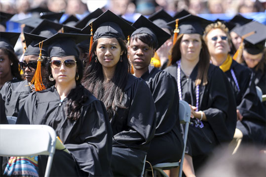Graduates sat outside during the University of Massachusetts Boston's commencement held in Dorchester.
