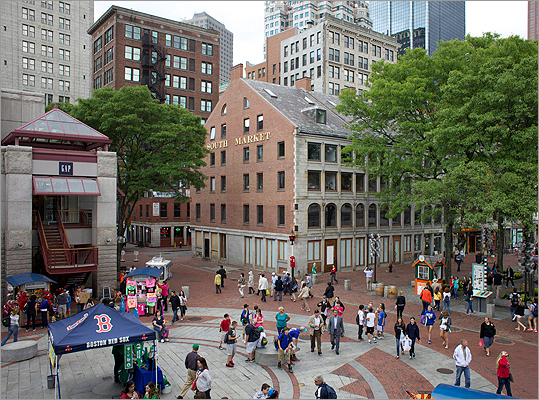 Shoppers walk passed the South Market building at Faneuil Hall Thursday afternoon in Boston.
