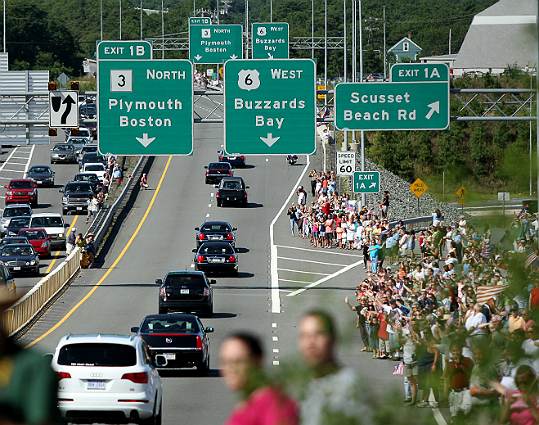 "Thousands lined overpasses and alongside highways as a hearse carrying Kennedy's casket made its way from his Hyannis Port home to the John F. Kennedy Presidential Library and Museum, where he lay in repose until his funeral. ""We're his family,"" said Teresa Antonelli, 82, who witnessed the senator's hearse pass by in the North End. ""We loved him so much. We'll miss him so much."" At left: Part of the motorcade transporting Sen. Edward M. Kennedy's body heads past the Sagamore Bridge on its way to the John F. Kennedy Presidential Library & Museum. Read more: Thousands line procession route to hail Ted Kennedy"