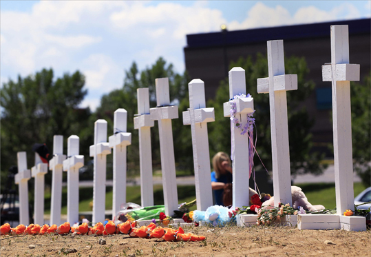 Crosses were seen at a memorial for victims behind the theater where a gunman opened fire on moviegoers.