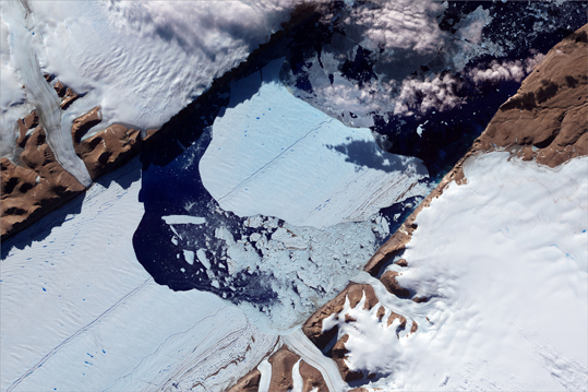 This NASA Earth Observatory image obtained July 27 shows the massive ice island as it broke free of the Petermann Glacier in northwestern Greenland. On July 16, the giant iceberg could be seen drifting down away from the floating ice block from which it came. The iceberg covers an area of about 12.5 square miles.