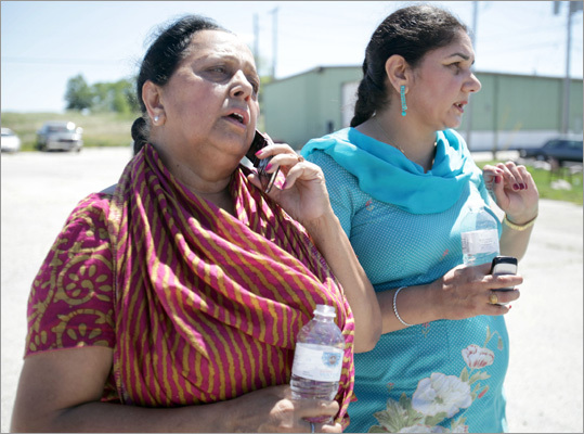 Parminder Kaleka, left, who said her brother-in-law was in the Sikh temple, used a phone to try to get more information.