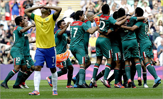 Brazil's Lucas (7) walked off dejectedly as Mexico's players began to celebrate their gold medal in soccer after a 2-1 victory.