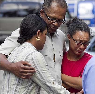 LaTeisha Adams (left), Rev. Gary Adams, and Danielle Bennett, relatives of Sharrice Perkins, slain Sunday night, consoled each other in Dorchester on Monday.