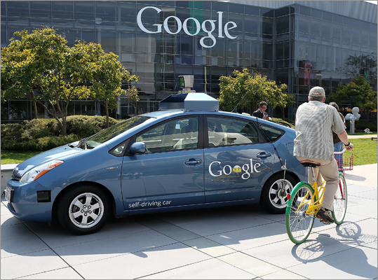 A bicyclist rode by a Google self-driving car at the Google headquarters on Sept. 25. California governor signs driverless cars bill
