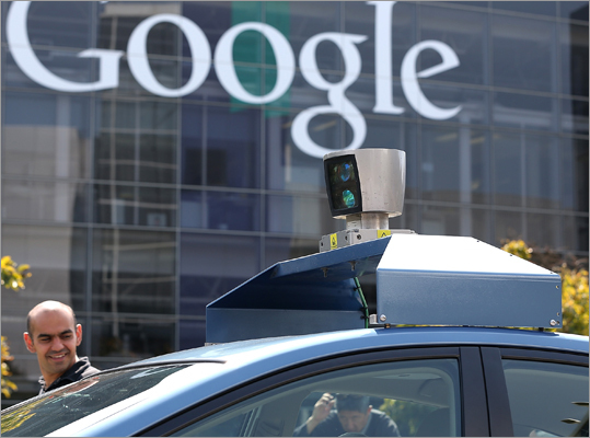 People looked at camera on top of a Google self-driving car. California governor signs driverless cars bill