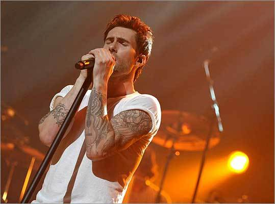 Since you can't hear his voice, we'll just go ahead and tell you. It's Adam Levine of Maroon 5, a coach on 'The Voice,' who also graced the cover of Ink magazine in September. Levine told the magazine the heart with a scroll that says 'mom' was done at Amsterdam's Hanky Panky.