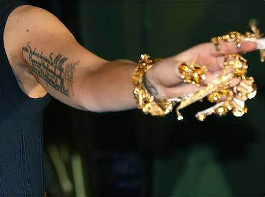 Which pop superstar has a German poet's words inked across her left arm?