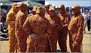 Tiger Woods supported by men in tiger costumes at British Open