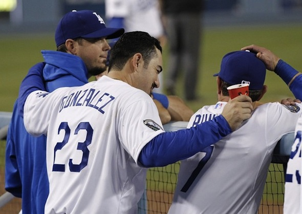 Los Angeles Dodgers first baseman Adrian Gonzalez (C) puts his arms around teammates pitcher Josh Beckett (L) and infielder Nick Punto (R) in the dugout during the fifth inning of an MLB baseball game against the Miami Marlins in Los Angeles August 25, 2012. Gonzalez, Beckett, and Punto were all acquired from the Boston Red Sox along with pitcher Carl Crawford in a nine player trade.