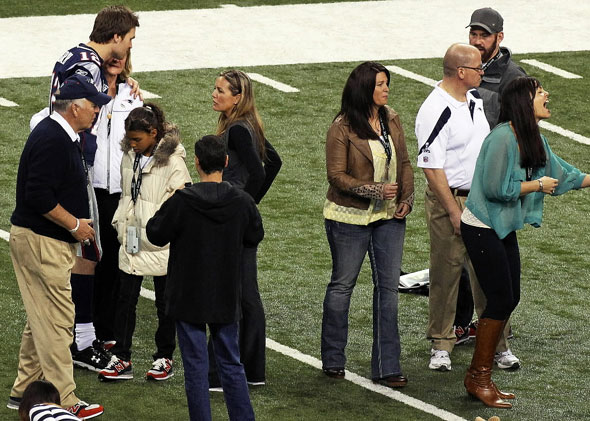 Kevin Youkilis (top right) with the Brady family, including Tom's three sisters and his parents on the field at Lucas Oil Stadium the day before the Super Bowl