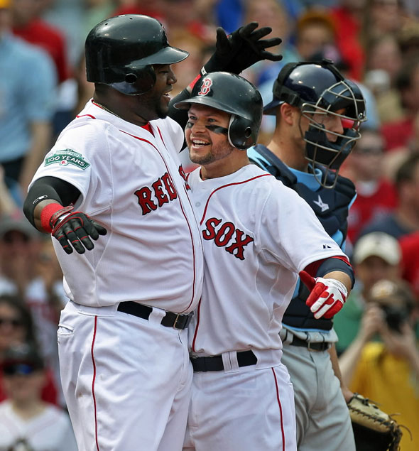 The Red Sox Cody Ross is welcomed home by teammate David Ortiz following his second inning three run home run that put Boston ahead 3-0. The Boston Red Sox hosted the Tampa Bay Rays in an MLB game at Fenway Park.